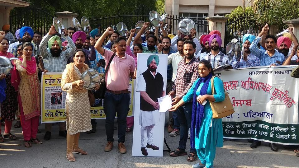 Teachers clinking utensils to stress that they are struggling due to non-payment of salaries — over which two of them are seen 'handing over' a memo to the CM's cutout — in Patiala.