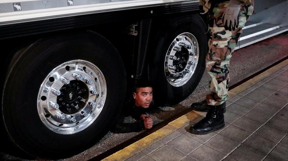 """""""Get down! Get down from there!"""" an officer with the coast guard's special forces yelled at the man peering at him from under a truck lined up for embarkation control, who was then handcuffed and escorted away at the port of Patras in Greece. (Alkis Konstantinidis / REUTERS)"""