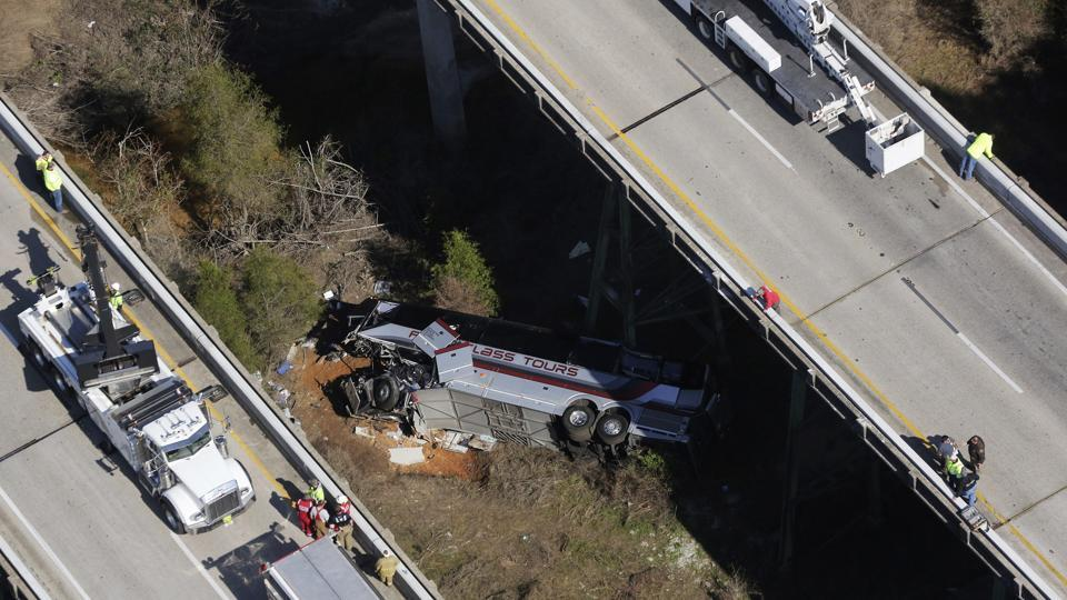 Rescue crews work at the scene of a deadly charter bus crash on Tuesday, March 13, 2018, in Loxley, Alabama. The bus carrying Texas high school band members home from Disney World plunged into a ravine before dawn Tuesday.