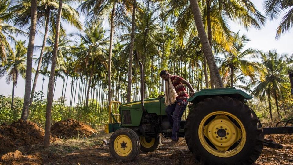 A farmer prepares to jump from a John Deere tractor, manufactured by Deere & Co., in the village of Kuragunda in Karnataka, India. After sweeping to victory with the help of the rural vote, Modi's popularity has taken a knock as farming incomes slumped, debts piled up, joblessness rose and suicides climbed.