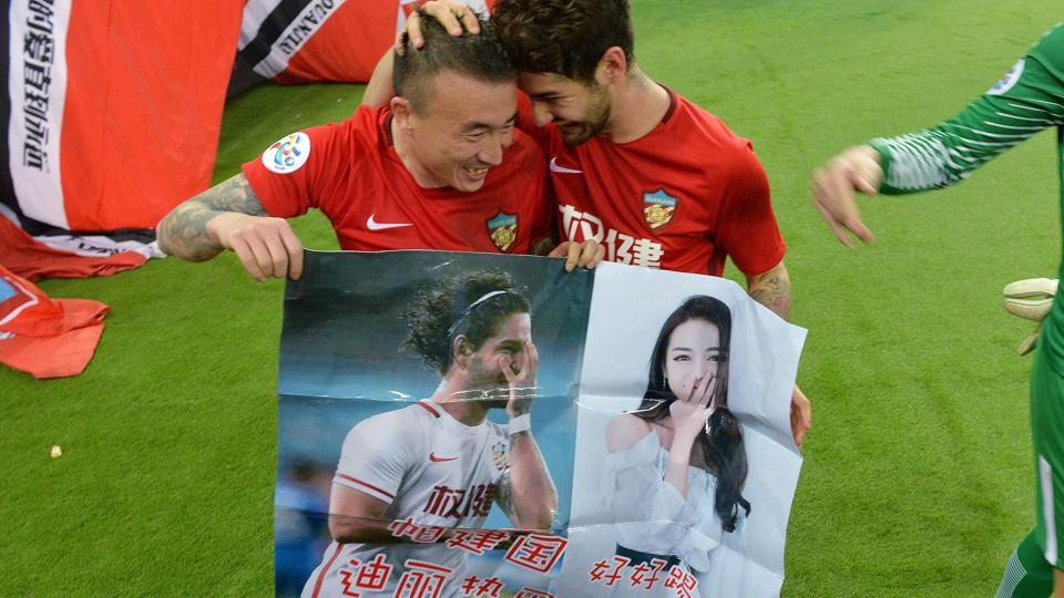 Alexandre Pato of Tianjin Quanjian (R), holding a poster showing pictures of him and Chinese actress Dilraba Dilmurat, with teammate Wang Yongpo.