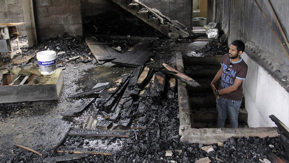 File photo of a man looking at a burnt home a day after anti-Muslim riots erupted in Digana, a suburb of Kandy.