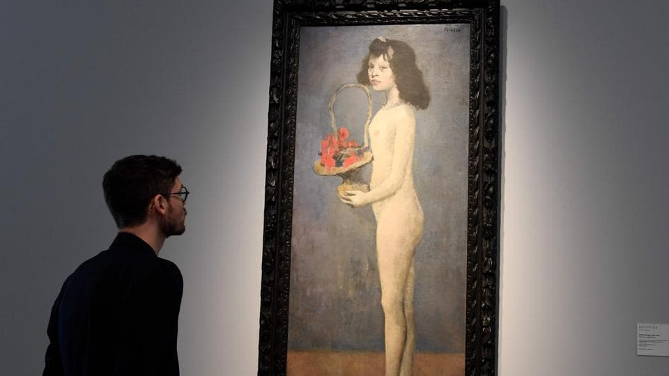 """A man looks at the painting """"Young Girl With a Flower Basket"""" 1905 by late Spanish painter Pablo Picasso at Christie's France, as part of a presentation of the collection Rockefeller in Paris on March 13, 2018, before the sale at Christie's New York."""