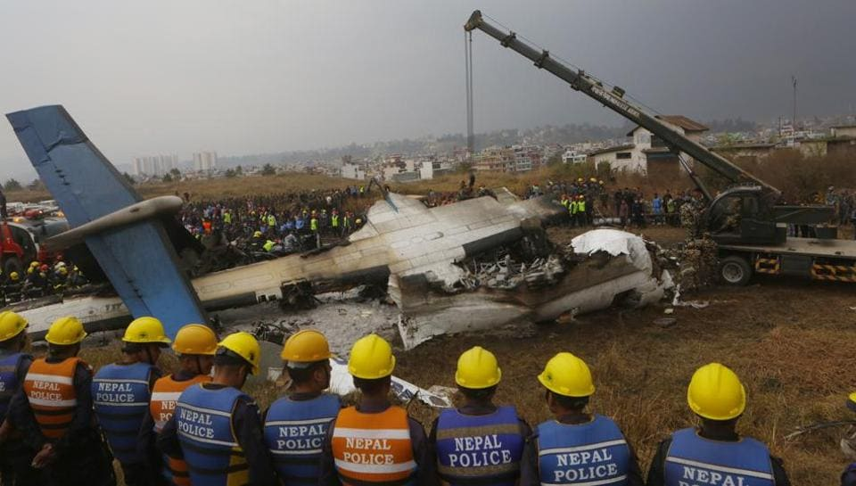 Nepalese rescuers and police near the debris of a passenger plane from Bangladesh that crashed at the airport in Kathmandu on March 12.