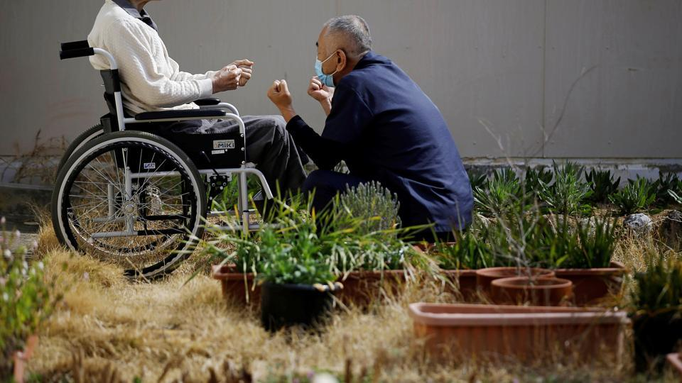 """A gaunt, 92-year-old man in a wheelchair sunbathes in a narrow courtyard, motionless. Nearby, a few dozen other elderly men hair exercise slowly as an instructor gently calls out, """"Don't strain yourselves."""" The man in the wheelchair is not in a nursing home. He is in prison, serving a life sentence for murder and rape. The others nearby are also serving time. (Toru Hanai / REUTERS)"""