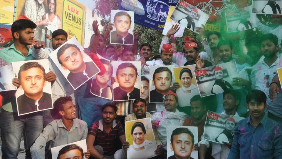 Supporters hold up photos of Samajwadi Party chief Akhilesh Yadav and Bahujan Samaj Party chief Mayawati to celebrate the their electoral victory in the Lok Sabha bypoll elections, at Lahurabir Azad Park, Varanasi on March 14, 2018.
