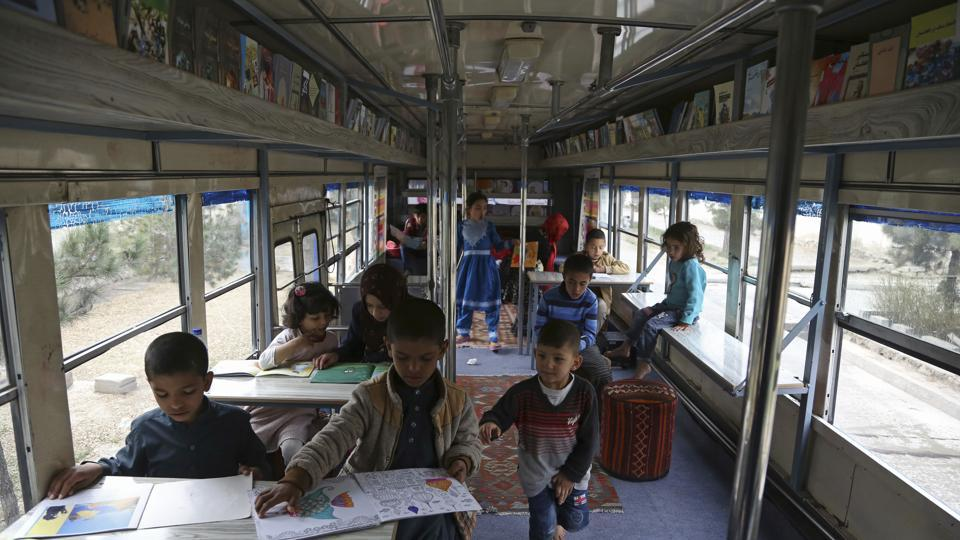 Afghan children read books in a library on wheels, in Kabul, Afghanistan. The mobile library was the initiative of 25-year-old Freshta Karim.