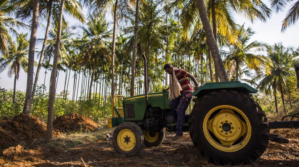 A farmer prepares to jump from a John Deere tractor, manufactured by Deere & Co., in the village of Kuragunda in Karnataka on March 8, 2018. (Prashanth Vishwanathan / Bloomberg)
