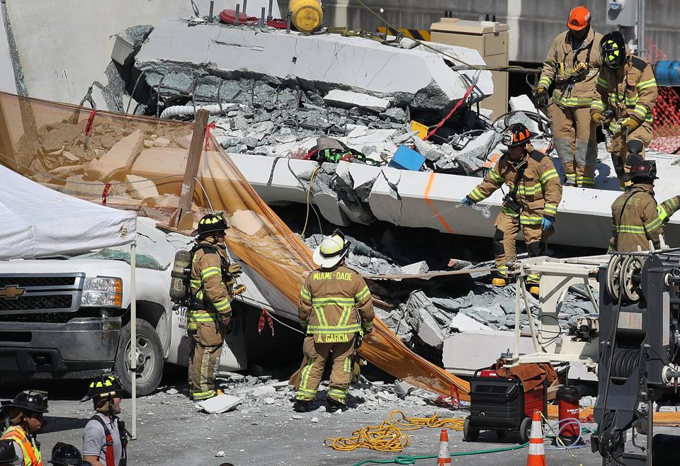 Miami-Dade Fire Rescue Department personnel and other rescue units work at the scene where a pedestrian bridge collapsed a few days after it was built over southwest 8th street allowing people to bypass the busy street to reach Florida International University on March 15 in Miami.