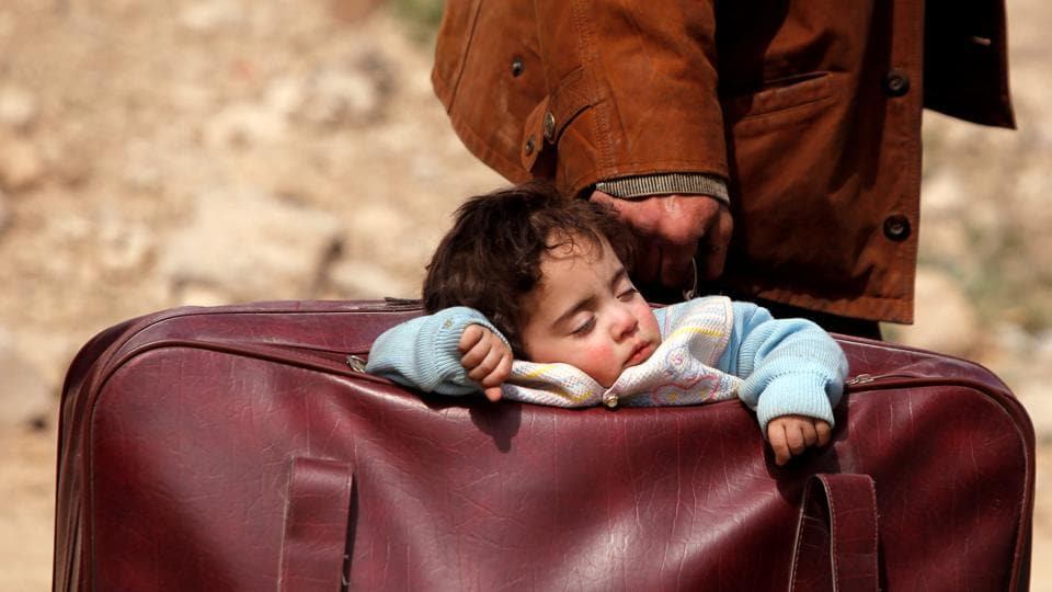 A sleeping child is carried in a bag in the village of Beit Sawa, eastern Ghouta, Syria. (Omar Sanadiki / REUTERS)