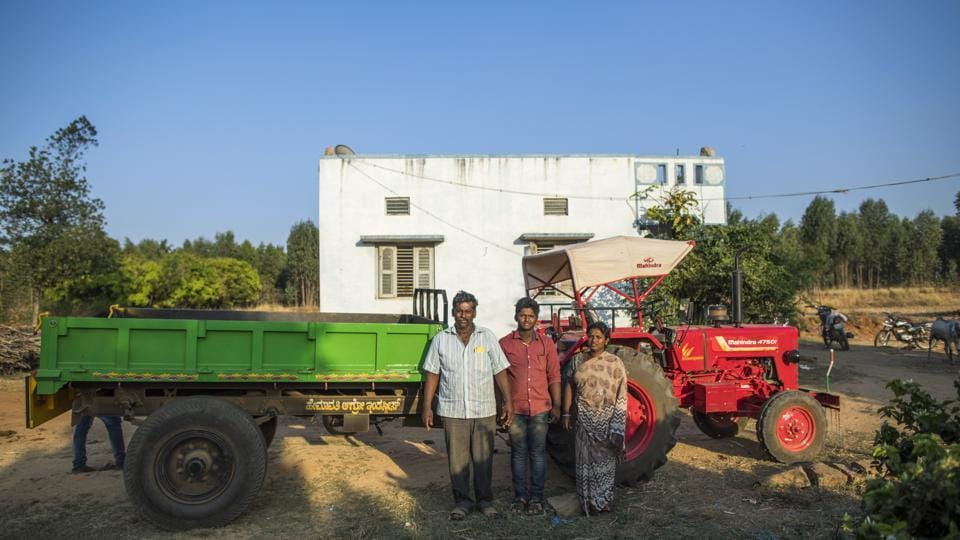 A farmer, left, stands with his family next to his newly purchased Mahindra 475 DI tractor, manufactured by Mahindra & Mahindra Ltd., outside his home in the village of Kuragunda in Karnataka, India, on Thursday, March 8, 2018. (Prashanth Vishwanathan / Bloomberg)