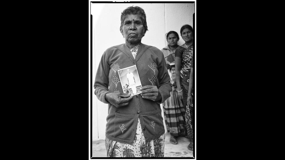 Ramanamma with a portrait of her deceased husband, A. Lakshmaiah, a tenant farmer from Mamillakunta Palli village. He committed suicide on July 25, 2015.  (Vijay Jodha)
