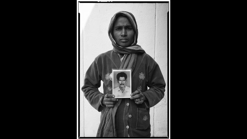 Yadamma with a portrait of her deceased husband Mallayya. There's an uncanny similarity between the women and the people in the photographs they're holding—their faces are grim in the wake of the agrarian crisis and its aftermath, the burden of life looming large before their eventual death. (Vijay Jodha)