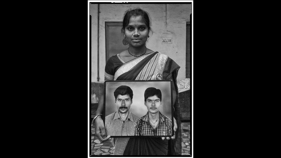 Devarajula Latha  with a framed photograph of her husband Devarajula Raju (left) and his younger brother, both of whom committed suicide in Telangana. (Vijay Jodha)
