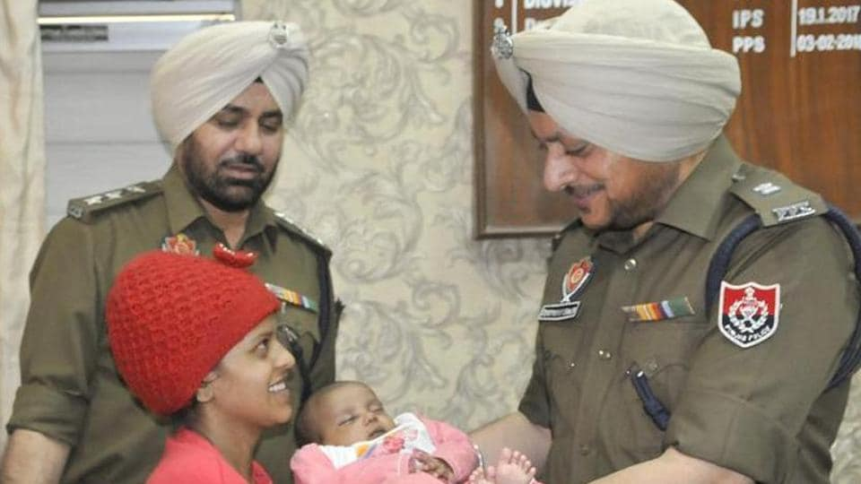 Police officials handing over the rescued child to his mother in Ludhiana.