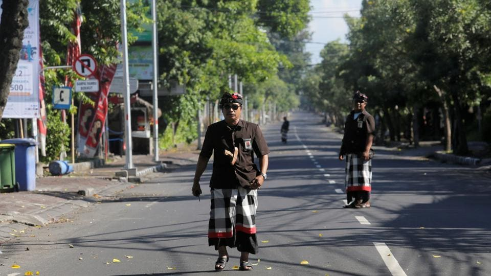 Balinese Hindu guards, known as Pecalang, patrol an empty road near Ngurah Rai International Airport on Nyepi, the Balinese day of silence, in Kuta, Bali, Indonesia March 17, 2018.