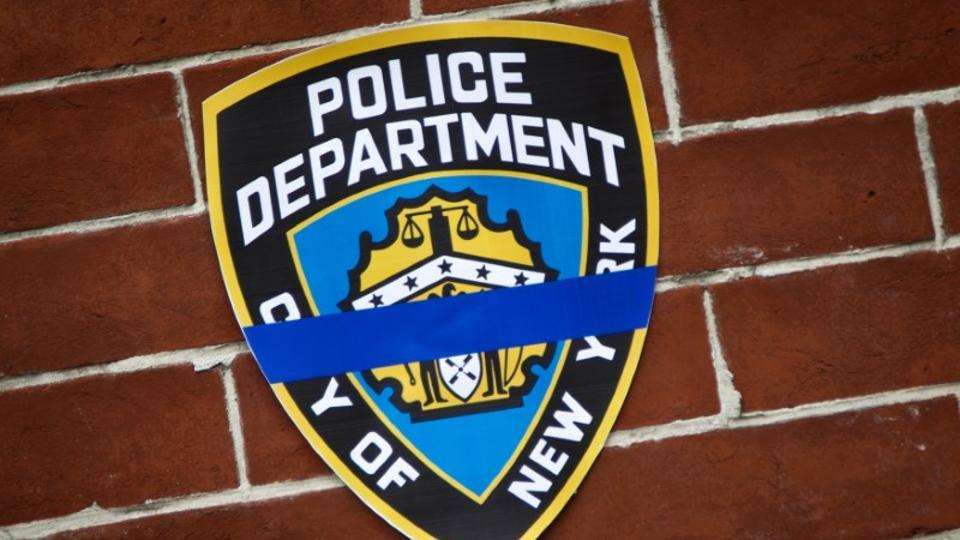 The NYPD logo pictured on a wall above a makeshift memorial in Brooklyn borough of New York.