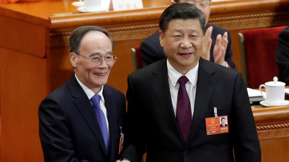 Chinese President Xi Jinping (R) shakes hands with newly elected Chinese Vice President Wang Qishan at the fifth plenary session of the National People's Congress (NPC) at the Great Hall of the People in Beijing, China March 17, 2018.