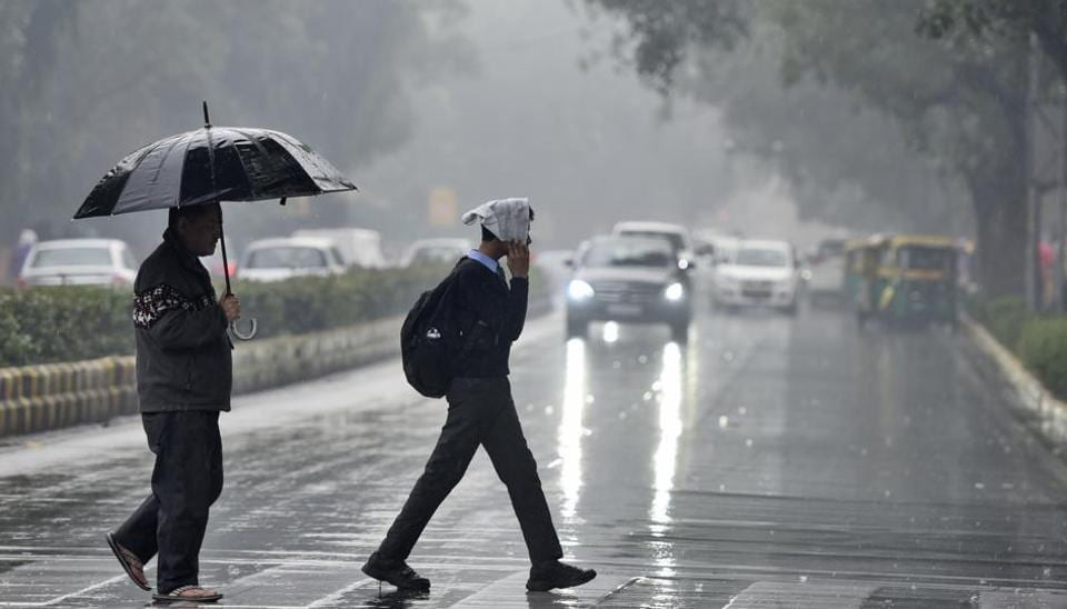 People cross a road during rain in New Delhi, India.