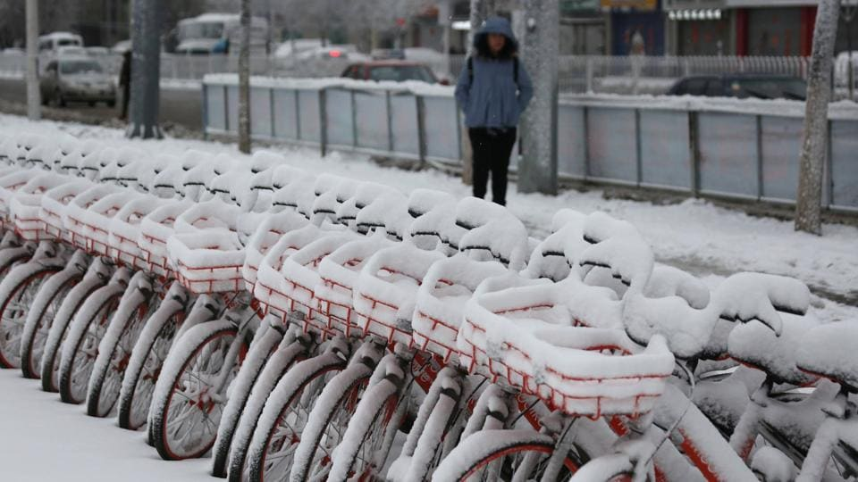 A woman walks past snow-covered bicycles of bike-sharing firm Mobike in Shenyang, Liaoning province, China, on March 15.