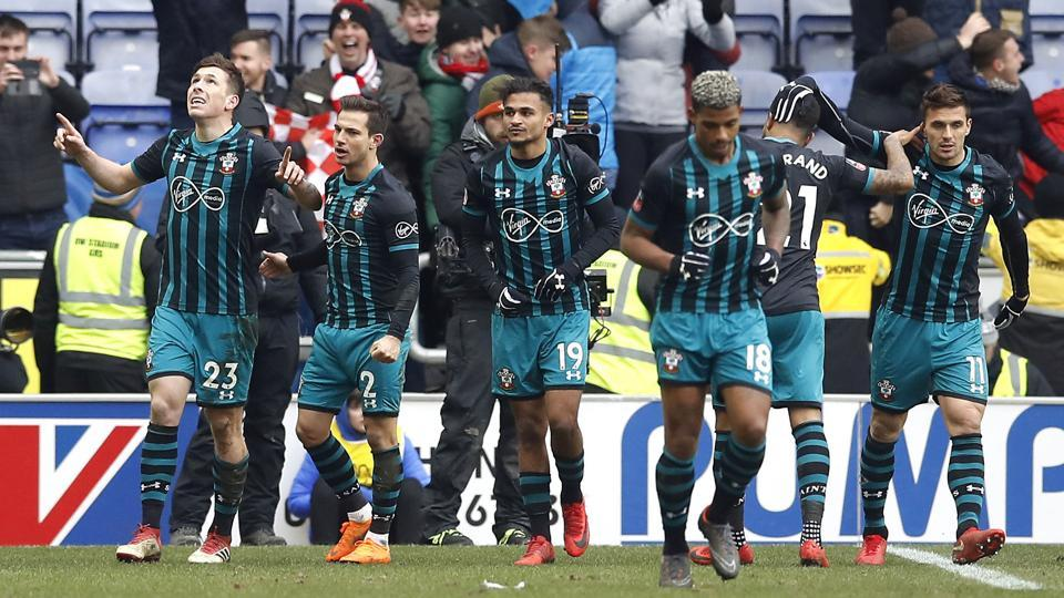 Southampton's Pierre-Emile Hojbjerg, left, celebrates scoring his side's first goal of the game against Wigan Athletic during theFA Cup quarterfinal at the DW Stadium in Wigan on Sunday.