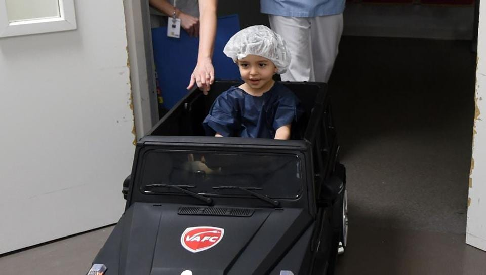 Two-year-old Souhail sits in an electric toy car on his way to the operating room at the Valenciennes Hospital in Valenciennes, northern France.