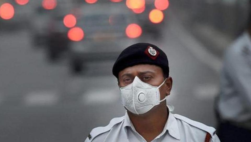 A traffic policeman wears a mask to protect himself from pollution, in New Delhi.