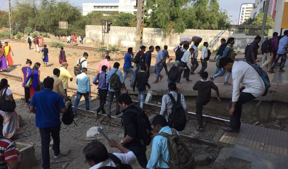 There were large crowds at stations on the harbour line. Here, people cross tracks at Vashi.