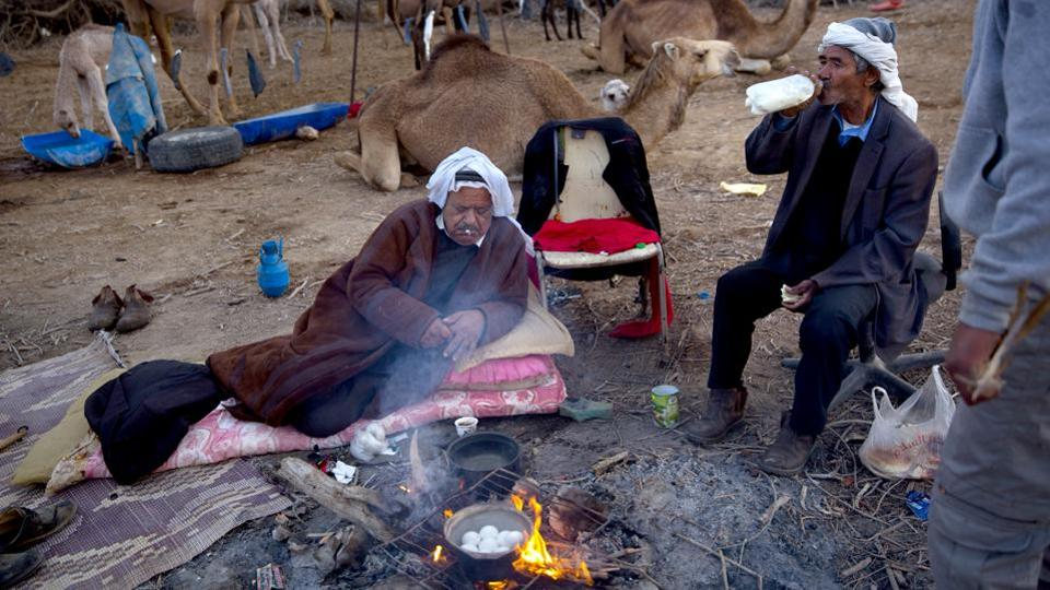 Camel owner Ali El Guran (L) and his herder Salem Rashaideh (R), have breakfast at their camp. Here they live simple routines, surviving mainly on bread and olive oil while drinking thick black coffee boiled on campfires. They sleep under the stars, near the herd, for weeks at a time without any cellphone coverage or other modern amenities. (Oded Balilty / AP)