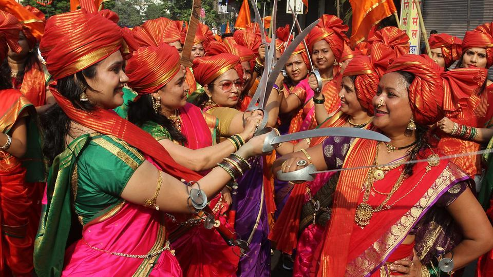 Women in colourful sarees, saffron turbans and mock swords in Thane. (Praful Gangurde/HT PHOTO)