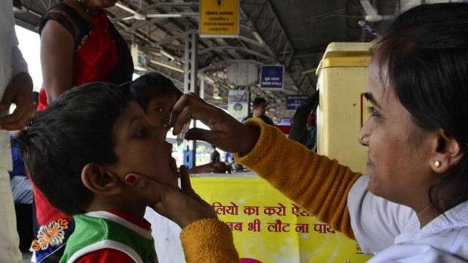 A boy  is being administered polio drops during a camp.