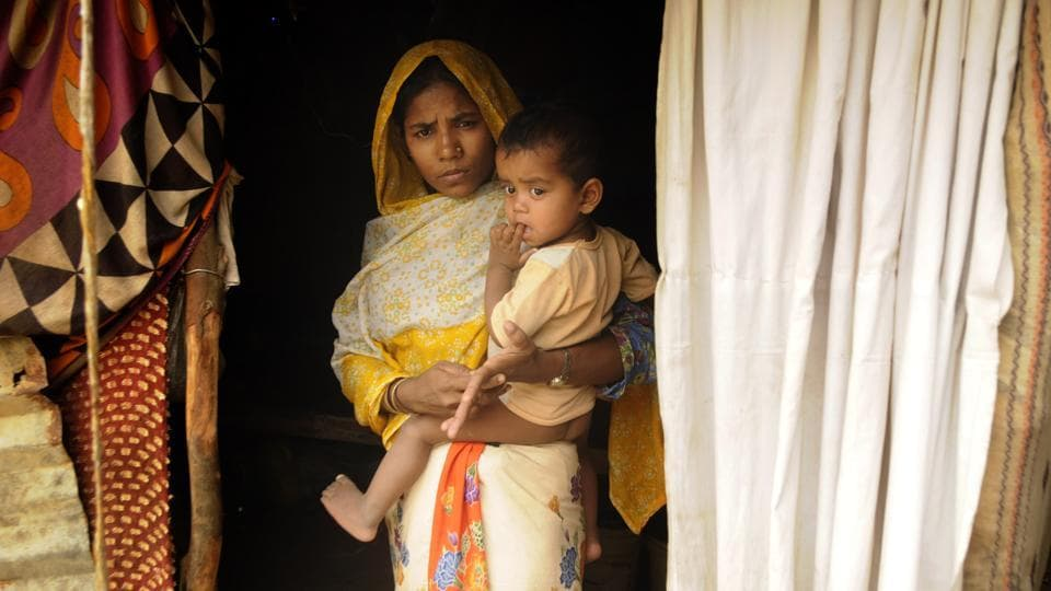 "Daiya Begum, a Rohingya refugee with her daughter poses for a photograph in front of her makeshift home in Baruipur, West Bengal. The Supreme Court directed the Centre to file a ""comprehensive status report"" giving details of conditions in Rohingya refugee camps in various states. The plea alleged that poor and unhygienic conditions at these camps have led to several deaths recently. (Samir Jana / HT File)"