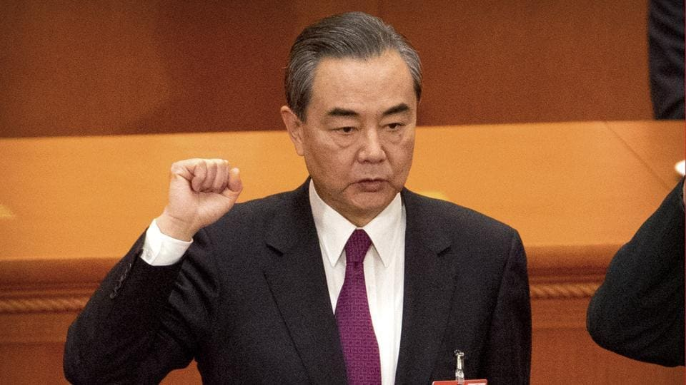 Foreign Minster and newly-appointed State Counselor Wang Yi takes the oath of office during a plenary session of China's National People's Congress (NPC) at the Great Hall of the People in Beijing on March 19, 2018.
