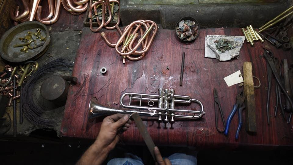A worker gives finishing touches to a trumpet. Aftab Ahmad, the grand old man of Meerut's brass instruments industry is now retired and family members look after the business. A living encyclopedia on wind instruments, Ahmad is credited with many innovations in the industry. From apprenticing at the Zildjian factory in Turkey to Dineley Rehearsals Studios on Baker Street, he has travelled the world to learn new technology, processes, and machinery. (Sanchit Khanna / HT Photo)