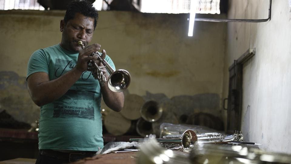 "Noor Alam tests a freshly minted trumpet at Nadir Ali & Co. in Meerut. Not happy with the pitch Alam changes position and blows harder, playing a popular Kishore Kumar tune. ""We don't have a testing laboratory here but I can instantly recognize a false note,"" the instrument tester said. (Sanchit Khanna / HT Photo)"