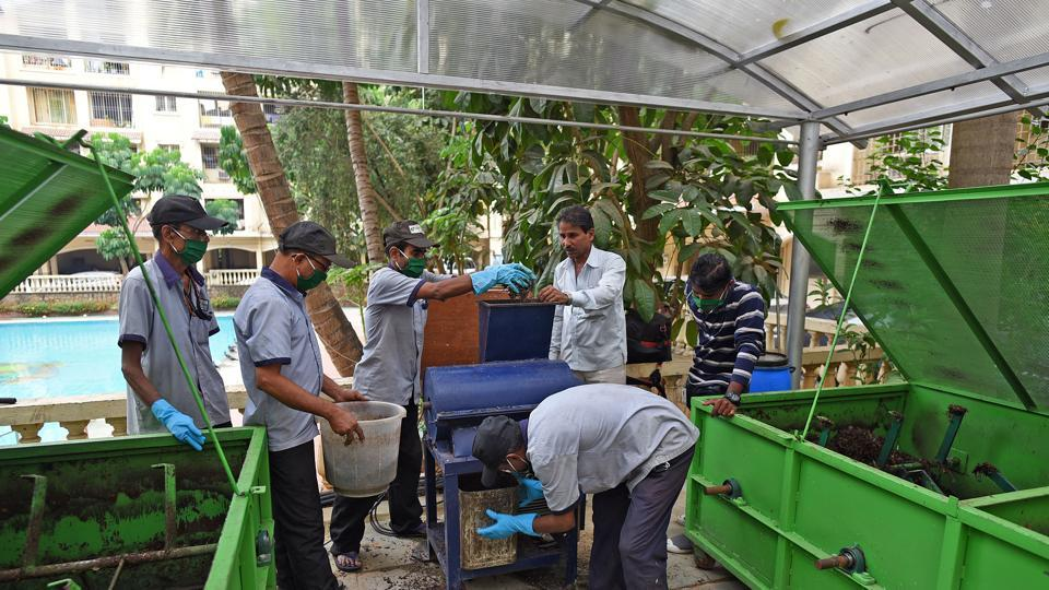 Workers process waste at a composting centre at the Valley of Flowers society in Kandivli.