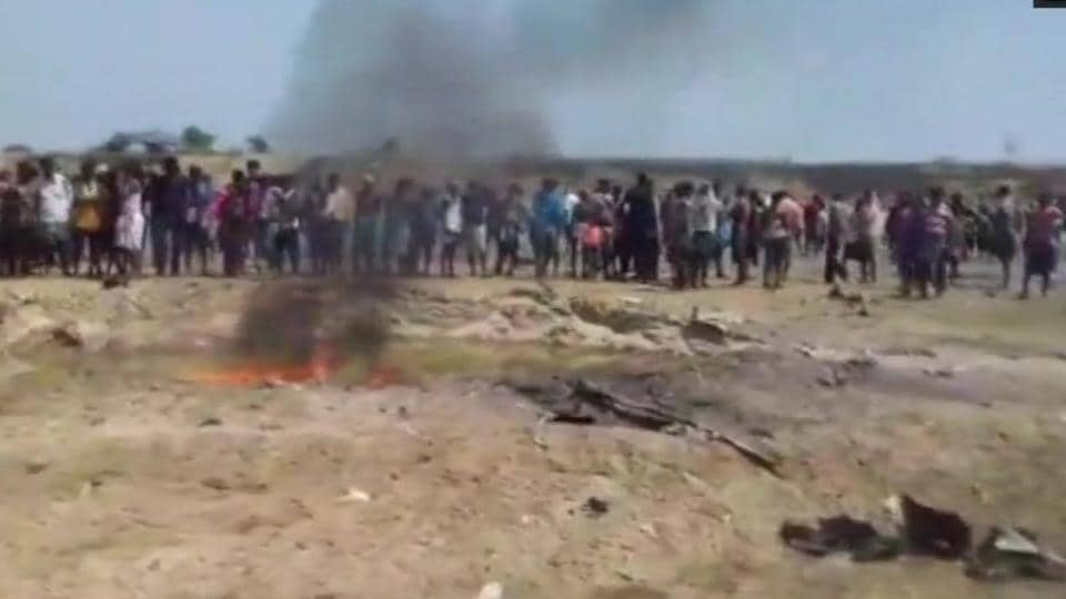 Locals watch the burnt remains of an IAFHawk trainer jet on the riverbed of the Subarnarekha on Tuesday.