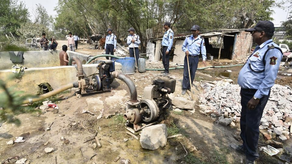 Guards on patrol assess a site on the floodplain where tube wells are being used. Thousands of gallons of groundwater are being extracted daily with the help of submersible pumps from the Yamuna floodplains — one of the few groundwater recharging zones left in Delhi — and supplied through tankers to commercial establishments in the city. (Sanchit Khanna / HT Photo)