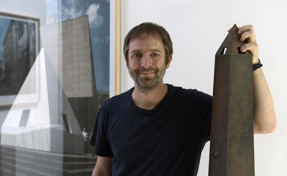 Argentine conceptual artist Leandro Erlich poses with a miniature reproduction of the Buenos Aires Obelisco.