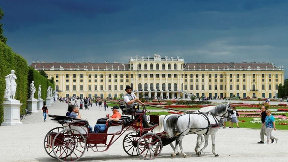 A traditional Fiaker horse carriage passes imperial Schoenbrunn palace in Vienna.