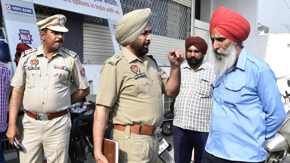 Police officials investigating after armed robbers loot Rs 18 lakh from collection agency employees outside a bank on Ferozepur Road in Ludhiana on Tuesday.