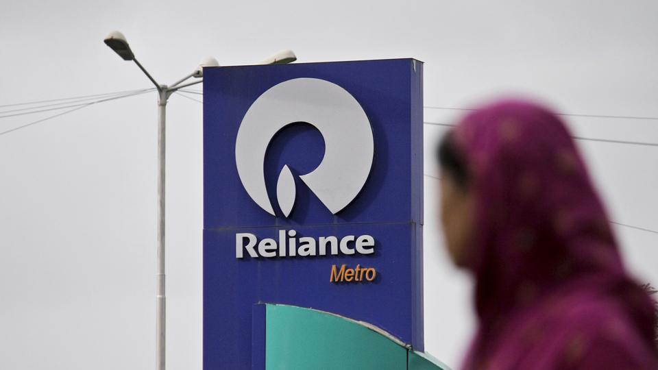 A woman walks past a Reliance Industries Ltd. gas station in Mumbai, India.