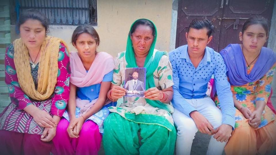 Family members of Balbir Chand, who has been missing in Iraq since 2014 and was not on the official list of 39 Indians declared dead, hold his photo at their residence in Selkiana village on Tuesday.