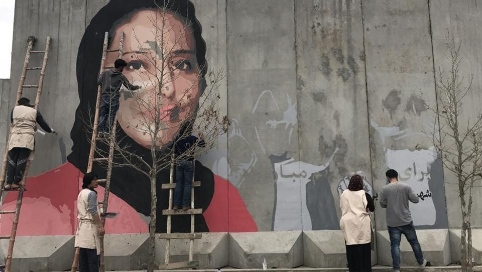 This handout from the Afghan social activist group ArtLords taken on March 8, 2018 shows artists painting a mural of Hamida Barmaki, who, along with her husband and children, was killed in a 2011 suicide attack on a supermarket, on a blast wall near the home of warlord Gulbuddin Hekmatyar, whose followers had carried out the attack, in Kabul.