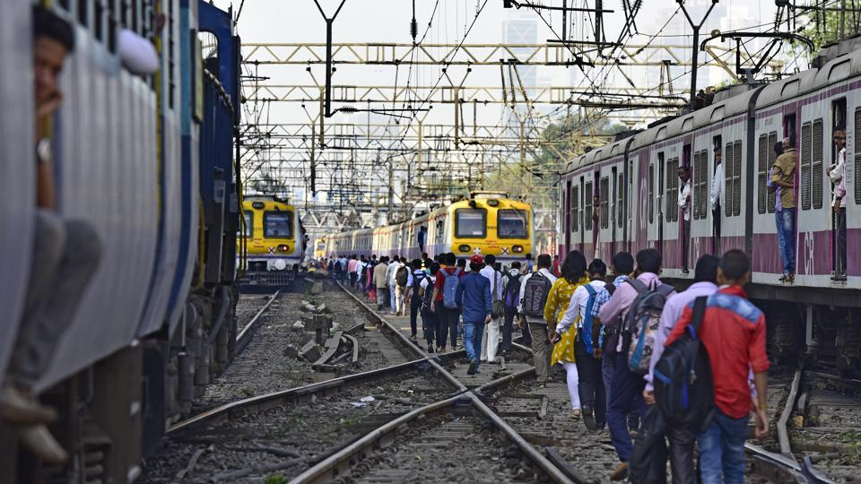 Commuters walk on the railway tracks between Sion and Matunga.