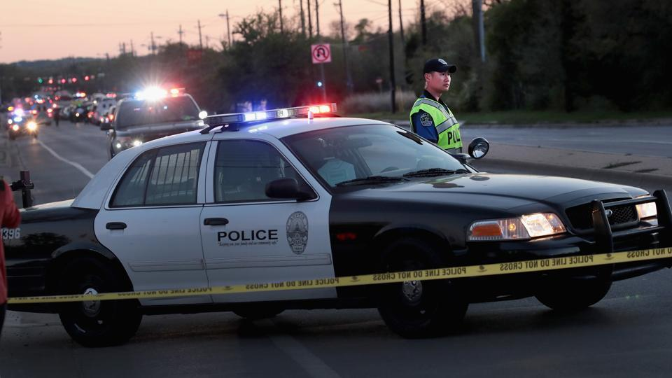 A police officer helps to secure the area after one person was injured by a package containing an incendiary device at a nearby Goodwill store on March 20, 2018 in Austin, Texas.