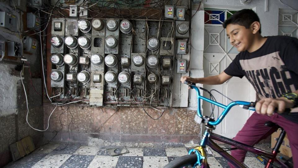 A boy living with his family in a tent camp on the street fetches his bike from inside a their damaged building at Independencia 18. Despite sunken floors and caved-in walls, residents need to enter daily to use the bathroom, shower, and retrieve stored belongings. (Rebecca Blackwell / AP)