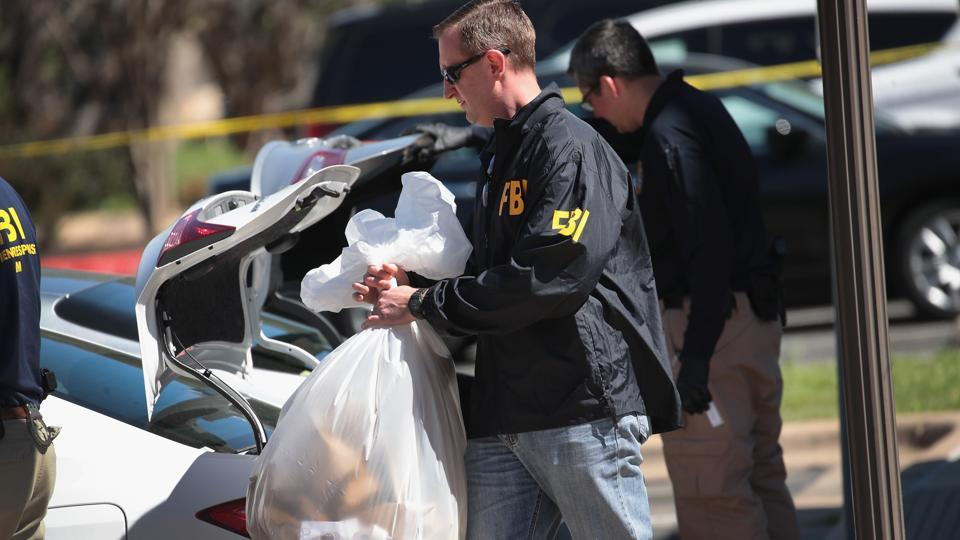 FBI agents collect evidence at a FedEx Office facility following an explosion at a nearby sorting center on March 20, 2018 in Sunset Valley, Texas.