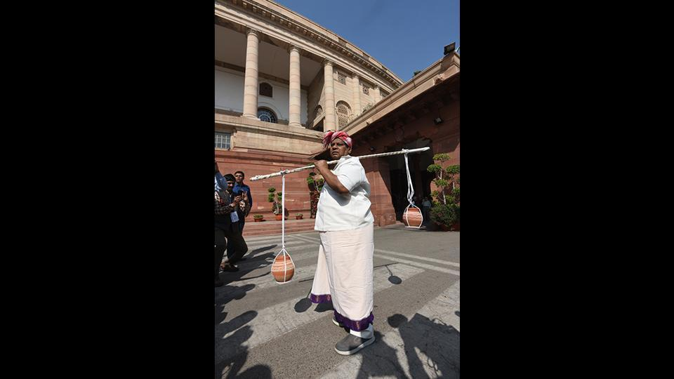 In a farmer's attire, Sivaprasad carried water and mud in earthen pots tied to a wooden twig as a part of his party's protest against the Centre for not granting Special Category status to Andhra Pradesh, during the second phase of budget session in New Delhi on March 07. (Sonu Mehta / HT Photo)