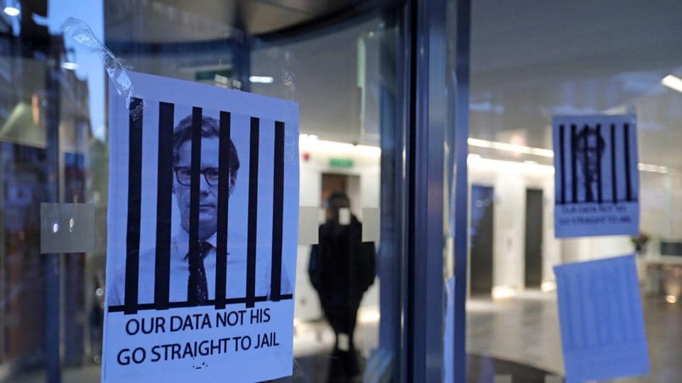 Posters depicting Cambridge Analytica's CEO Alexander Nix behind bars, with the slogan 'Our Data Not His. Go Straight To Jail' are pictured at the entrance of the company's offices in central London on March 20, 2018.